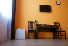 Compact White Refrigerator, A Table, Two Chairs, An Electric Kettle And A Wall-mounted TV In The Interior Of A Small Studio Apartment Or Hotel Room