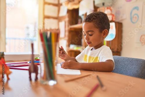 Obraz Beautiful african american toddler sitting painting car toy using marker pen on desk at kindergarten - fototapety do salonu