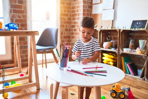 Fototapeta Beautiful toddler boy drawing cute draw using colored pencils at kindergarten obraz na płótnie