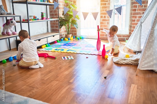 Obraz Adorable blonde twins playing around lots of toys at kindergarten - fototapety do salonu