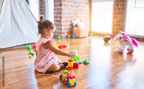 Obraz Young beautiful toddler sitting on the floor playing with small cars toys at kindergaten - fototapety do salonu