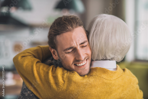 Canvas-taulu Young handsome man in camouflage hugging his mom