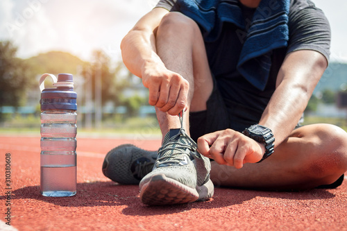 Photographie Man runner tying shoelaces on track stadium.