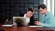 Young man showing smartphone to coworker at office. People discuss job at the table with laptop in workplace. Concept of teamwork young business people. Tracking shot in slow motion.