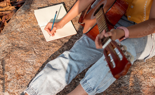 Obraz na plátně Songwriter writing on notebook with acoustic guitar.