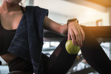 Woman Holding Apple After Fitness Exercise At Gym. Healthy And Lifestyle Concept.