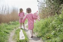 Two Girls Walking In Meadow
