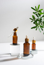 Natural Cosmetic Skincare Or Essential Oil Bottles Container And Green Leaf On White Background. Home Made Remedy And Beauty Product Concept.
