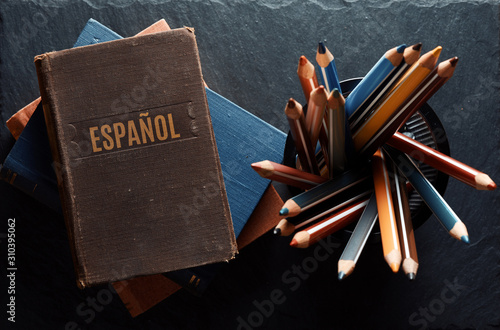 Fototapeta learninf Spanish concept. Old books and pencils