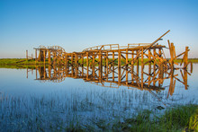 Destroyed Wooden Bridge Over A Small River. Evening Sunset.