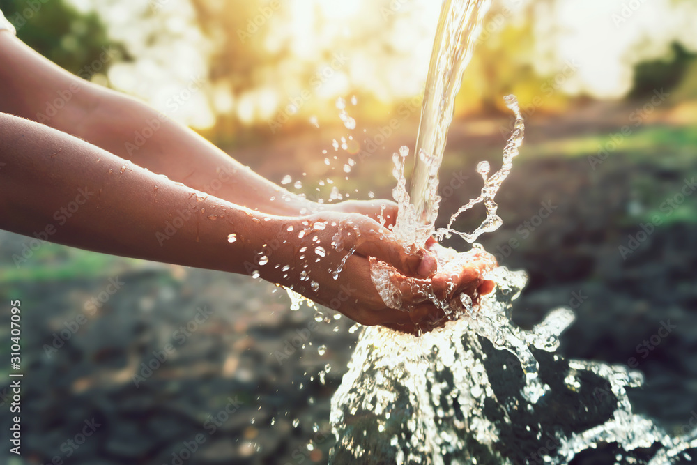 Fototapeta Water pouring on hand in morning ligth background