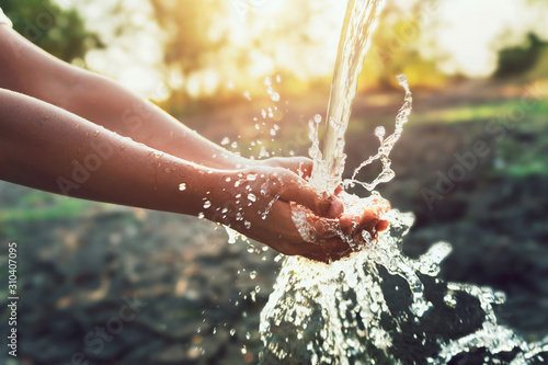 Fotomural  Water pouring on hand in morning ligth background