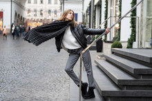 European Lively Young Girl In Gray Textile Pants, An Oversized Warm Leather Jacket, Nubuck Uggs And A Large Scarf Actively Posing On Steps Near Store. Life Style