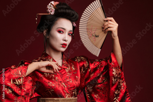 Fotografía Image of young geisha woman in japanese kimono holding wooden hand fan