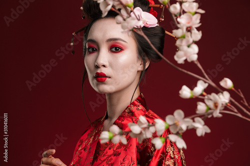Image of geisha woman in traditional japanese kimono with sakura tree Fototapeta
