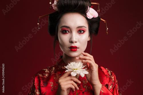 Fotografie, Tablou Image of beautiful geisha woman in japanese kimono holding flower