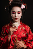Image of beautiful geisha woman in japanese kimono holding flower