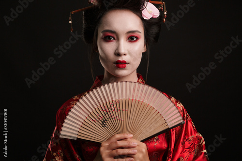 Tablou Canvas Image of young geisha woman in japanese kimono holding wooden hand fan
