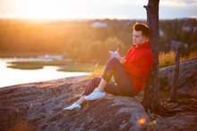Young Man In Hoodie Sitting On Top Of The Rock, Writing In The Notebook. Beautiful Sunset Landscape. Man Get Inspired By Nature. Finland, Espoo