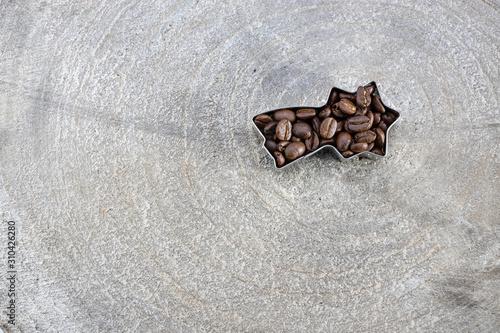 Photo Braune Kaffee Bohnen in einer Form als Sternschnuppe auf einem Holz Brett Scheib