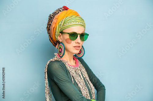 Beautiful woman with a turban on her head, fashion earrings and a bracelet Fototapeta