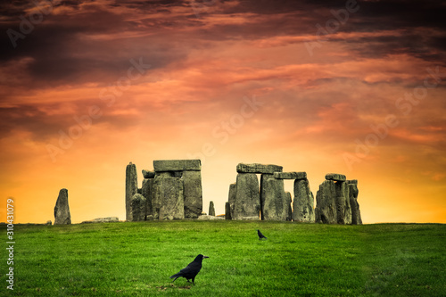 Cuadros en Lienzo Historic Stonehenge under colorful sunset with black crows