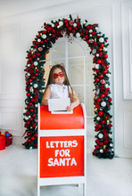Funny Little Girl With Cat's Ears Stands Near Mailbox Indoors.