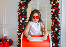 Funny Little Girl In Red Eyeglasses Sent Letter To Santa Claus With List Of Christmas Gifts.