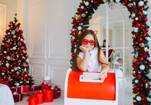 Funny Child Girl Sends A Letter To Santa Claus. Preparing For Christmas And Ordering Gifts From Santa.