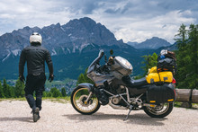 Back View Of Biker With Adventure Touring Motorcycle In Full Equipment On Dirt Road, High Top Mountains On Background, Tourism Travel Concept, Copy Space. World Riders