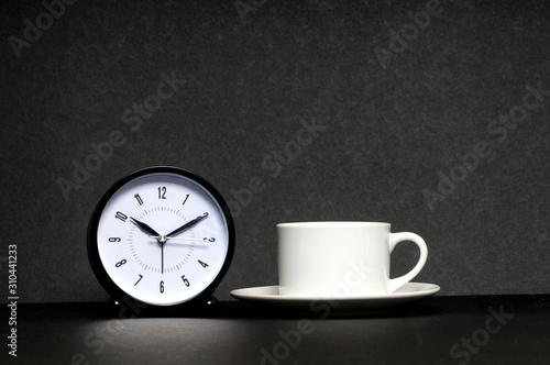 Leinwand Poster Time for a Break. Coffee cup with clock on black background