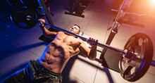 Bodybuilder Trainer Man Doing Bench Press Workout In Gym. Video From The Top. Blue Light Filter. Naked Torso. Strong Abs. View From Above. Closeup.