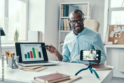 Fototapeta Intelligent young African man in shirt showing chart and telling something while making social media video obraz