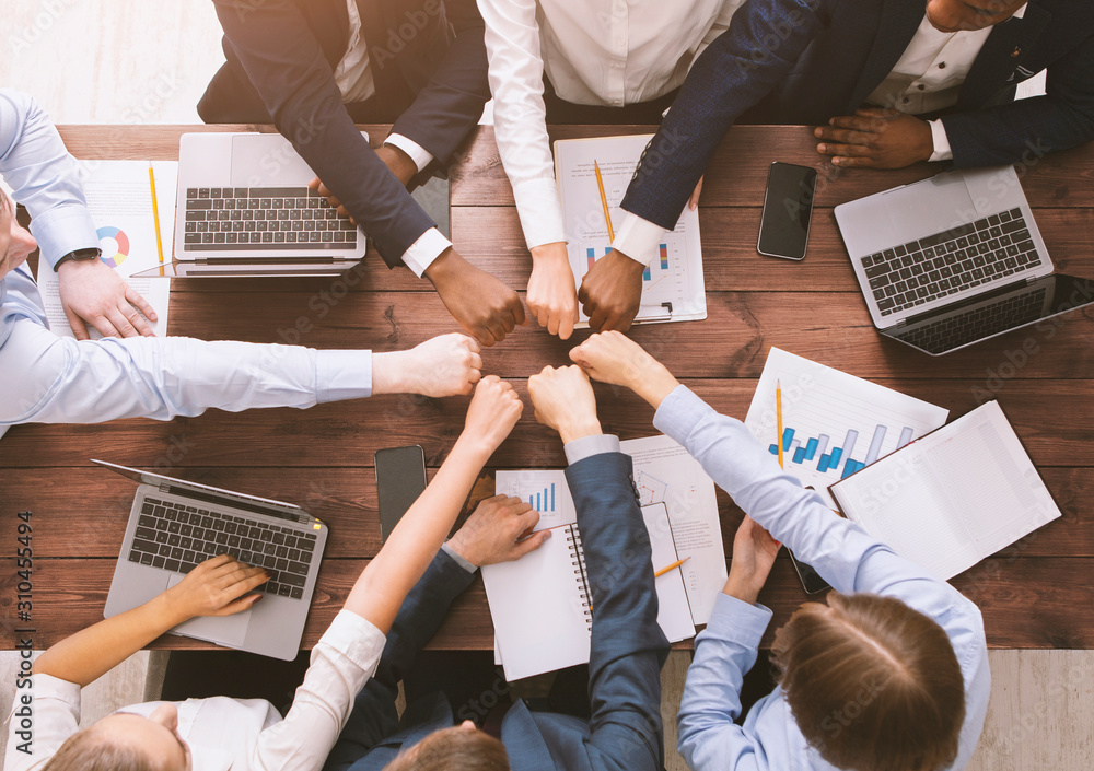 Fototapeta Fist bump of corporate team at meeting in office, top view