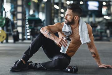 Fototapeta na wymiar Pensive bodybuilder with water sitting on floor at gym