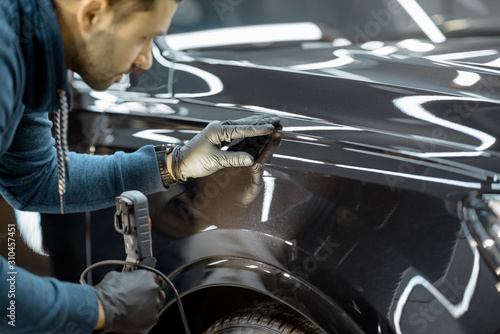 Fotomural Car service worker examining vehicle body for scratches and damages, taking a car for professional auto detailing