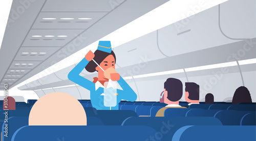 stewardess explaining for passengers how to use oxygen mask in emergency situati Canvas Print