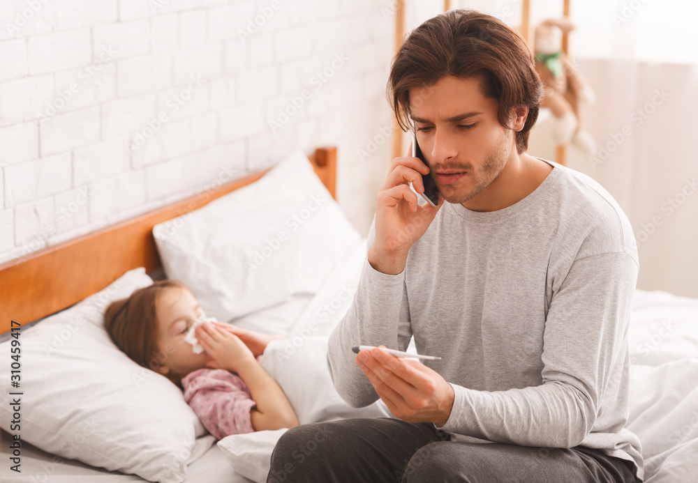 Father checking his daughter's temperature, calling doctor