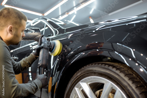 Worker polishing vehicle body with special grinder and wax from scratches at the car service station Fototapet