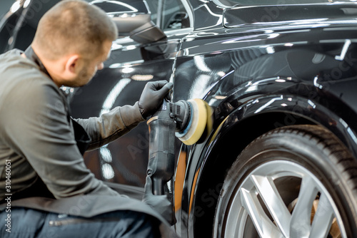 Fototapeta Worker polishing vehicle body with special grinder and wax from scratches at the car service station. Professional car detailing and maintenance concept obraz