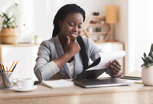 Pensive Black Businesswoman Checking Financial Reports At Workplace In Office