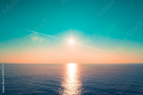 Sun is setting and reflected in an open ocean water sea bay for nature background and backdrop.