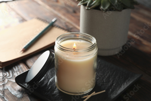 Burning candle in glass jar, succulent and notebook on wooden background, close up