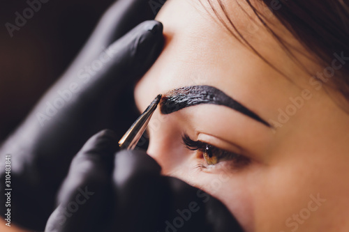 beautician- makeup artist applies paint henna on previously plucked, design, trimmed eyebrows in a beauty salon in the session correction Wallpaper Mural