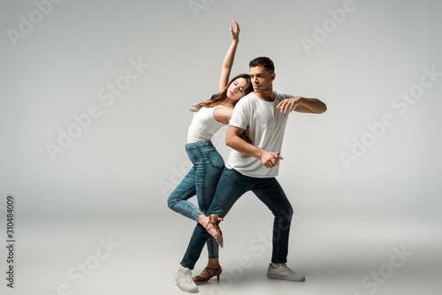 Obraz na plátne dancers with closed eyes dancing bachata on grey background
