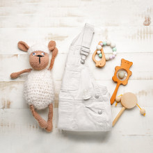 Baby Clothes And Toys On White Wooden Background