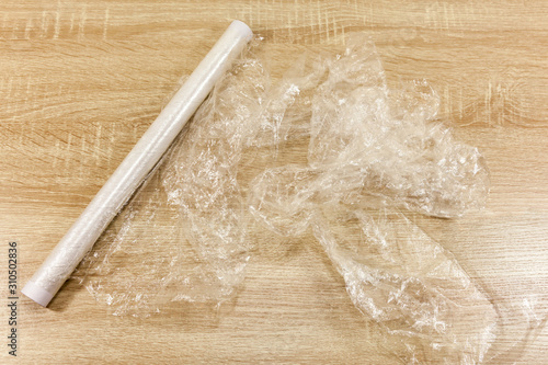 Valokuvatapetti Roll of cling film on a wooden worksurface