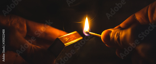 A match lit in the dark in hands with a matchbox Canvas Print
