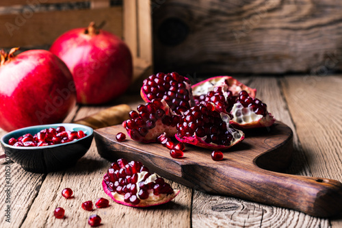 Fototapeta Fresh ripe whole pomegranates,  opened pomegranate  and  seeds obraz