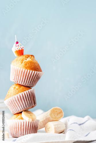 Fotografie, Obraz Stack of banana muffins in white paper muffin cups close-up, blue background